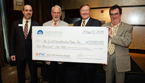 Roger Harman '66 (second from left) and partner Vince Whittacre (far right), accepting award check